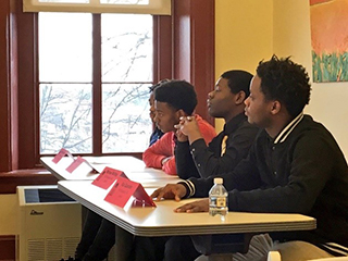 Four male students listening intently in a classroom