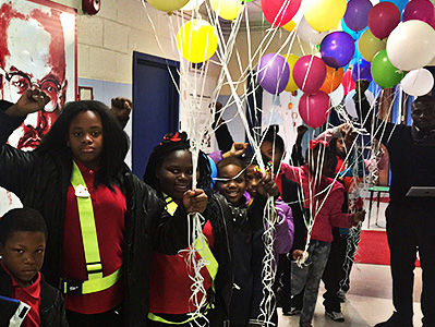 Students hold multi-colored balloons in the hallway. at their school.