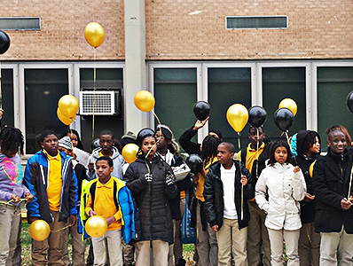 Students release balloons colored gold and black, their school colors.