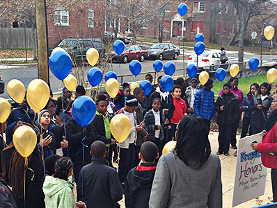 Students hold blue and gold balloons outside of their school.