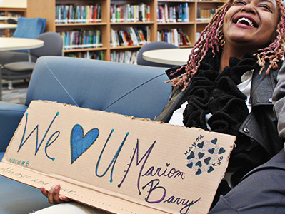 "Woman holds a sign that reads We ""Heart"" U Marion Barry"