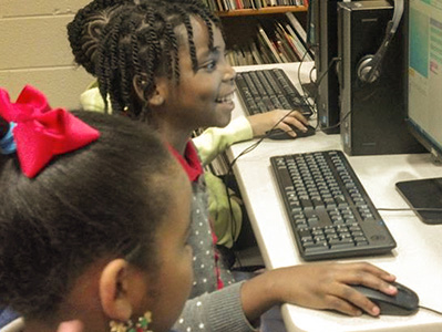 Elementary school students smile while seated at computers