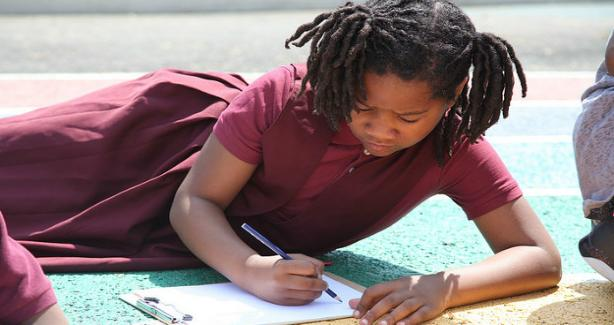 A child laying on the blacktop, drawing