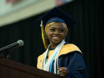 Student in a cap and gown standing at a podium during graduation