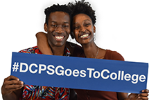 Two smiling students holding a #DCPSGoesToCollege sign