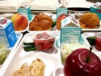 Photo of a school lunch trays with grilled chicken, asparagus, peppers, a croissant, an apple and a small carton of milk.