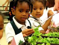 Photo of two elementary school girls making salads from three bowls of different greens.