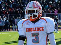 Photo of a male student football player wearing a white and orange Coolidge High School helmet and jersey on the football field.