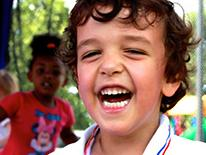 Photo of a smiling male pre-kindergarten student wearing a white shirt