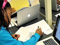 Photo of young girl doing work on paper and on computer