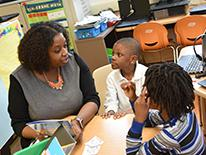 Photo of a woman speaking to two children in a classroom