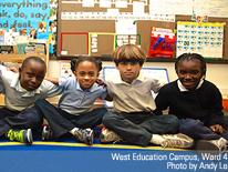 four elementary school students sitting on the floor with their legs crossed and arms on each others shoulders.