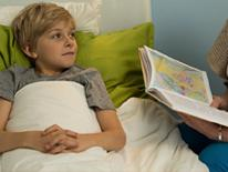 Photo of young student in bed being read to