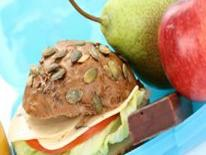 Image of whole grain sandwich with lettuce tomato and cheese, a pear, an apple and a chocolate brownie